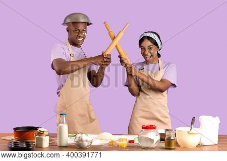 Silly African American Couple Having Mock Fight With Rolling Pins While Baking In Kitchen, Lilac Stu