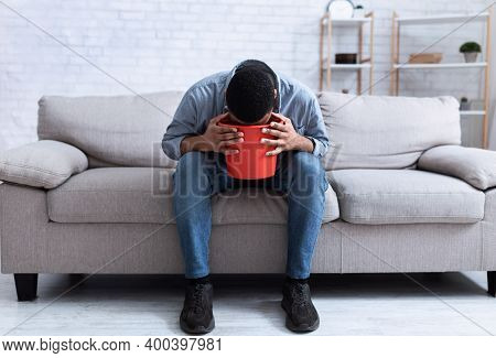 Unrecognizable African American Man Vomiting Into A Bucket Sitting On Couch At Home. Intoxication, P