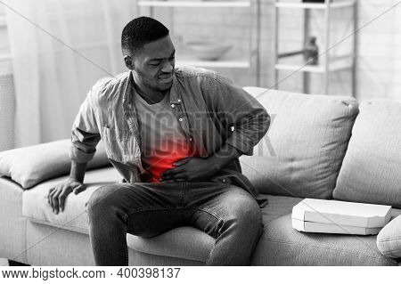 Stomachache. African Man Touching Aching Abdomen With Red Inflamed Zone Having Stomach Pain After Ea