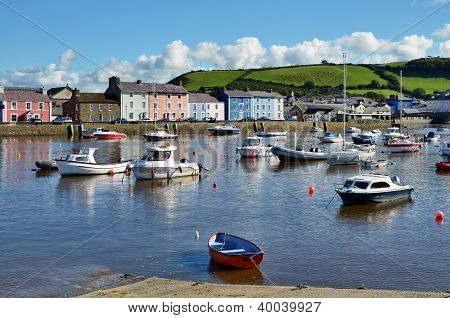 Boats in Aberaeron Harbour, Wales, with colourful regency style houses lining the quayside, against a backdrop of a grassy hillside poster