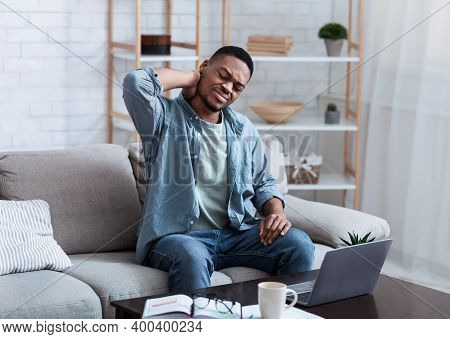 Neck Pain. African American Man Massaging Aching Neck Suffering From Ache Sitting And Working At Lap