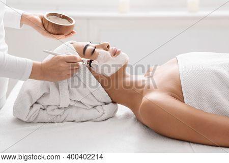 Skin Lifting Treatment. Young Asian Woman Getting Facial Nourishing Mask By Professional Beautician