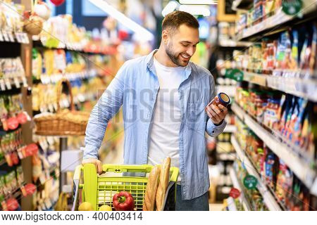 Consumption Concept. Portrait Of Smiling Bearded Guy With Shopping Cart In Market Buying Groceries F