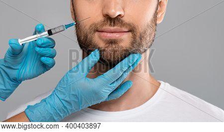 Unrecognizable Bearded Man Getting Lips Filler In Beauty Salon, Grey Studio Background, Cropped. Clo
