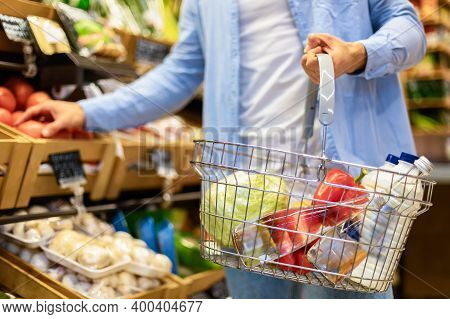Grocery Shopping. Closeup Of Unrecognizable Male Customer Holding Cart Basket Full Of Food And Choos