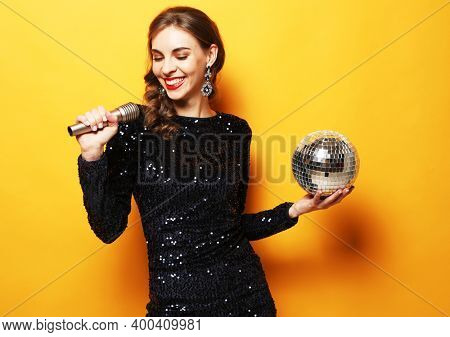 Party, holiday and celebration concept: Young brunette woman with long curly hair dressed in evening dress holding a microphone and disco ball