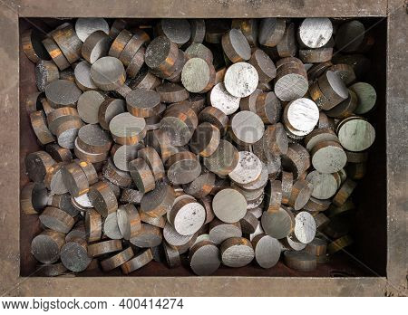 A Pile Of Sawed Short Cylindrical Steel Workpieces. Close-up Industrial Background.