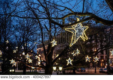 The City Is Decorated For The Holiday. Christmas Decoration On The Trees. Glowing Lamps In The Form