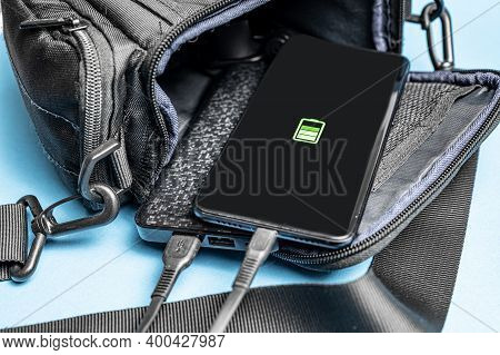 Close-up Of Charging A Smartphone From A Power Bank. The Phone And The Power Bank Are In An Open Bag