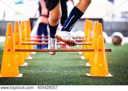 Selective Focus To Cone And Hurdles Marker With Blurry Kid Soccer Player Jogging And Jump Cross It.
