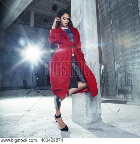 Young Pretty African American Woman In Luxury Red Coat Posing Fashionable On Empty Parking Building,