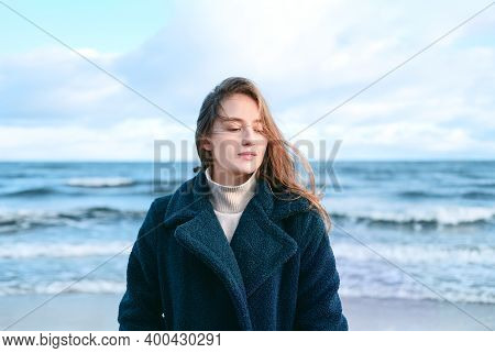 Young Beautiful Woman Braving A Cold Winter Day At The Seaside. Happy Female With Long And Flying Ha