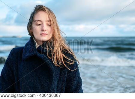 Portrait Of Young Beautiful Woman Braving A Cold Winter Day At The Seaside. Happy Female With Long H