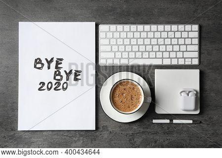 White Sheet Of Paper With Phrase Bye Bye 2020 Near Coffee, Keyboard And Wireless Earphones On Grey T