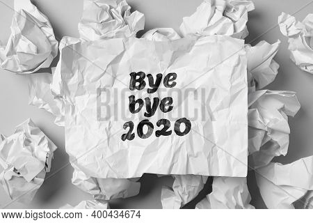 Crumpled Sheet With Phrase Bye Bye 2020 Among Paper Balls On Light Grey Table, Flat Lay