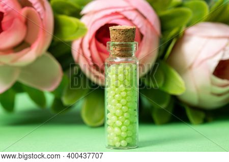 Glass Bottle With Green Granules And Roses In The Background. Homeopathic Remedies