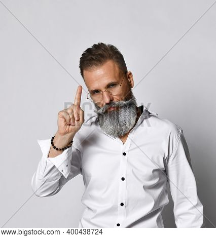Portrait Of A Stylish, Handsome And Smart Hipster Man Who Raises His Finger Up On A White Background