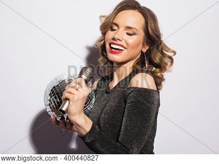 young blond woman dressed in evening dress holding a microphone and disco ball, singing and smiling