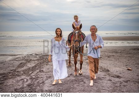 Little Pretty Girl On A Horse. Father And Mother Leading Horse By Its Reins On The Beach. Horse Ridi
