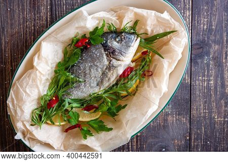 Dorada With Lemon, Aromatic Herbs On The Background Of A Dark Wooden Table