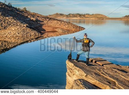 male canoe paddler with a paddle on  a rocky shore of a mountain lake - Horsetooth Reservoir in northern Colorado in fall or winter scenery