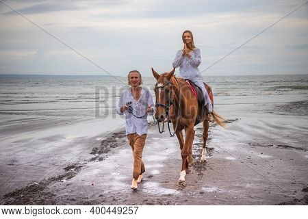 Horse Riding By The Sea. Woman On A Brown Horse. Hands In Namaste Mudra. Man Leading Horse By Its Re