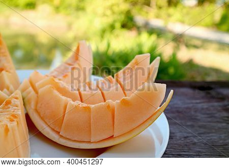 Plate Of Slices Of Mouthwatering Fresh Cantaloupe Melon On The Garden Wooden Table