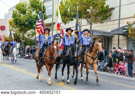 SAN FRANCISCO, USA - OCTOBER 11, 2009: Columbus Day celebration. Equestrian parade in honor of the national holiday. Dressy riders in cowboy hats carry US flags on well-groomed horses