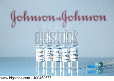 Johnson And Johnson Vaccine Against Covid-19. Glass Medical Vials With Liquid On The Background Jons