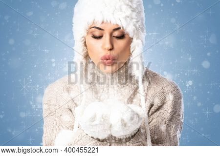 Young Beautiful Woman Wearing Winter Hat And Mittens Over Blue Background, Blowing Snow With Hands,