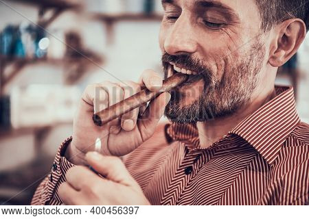 Man Sits With A Cigar In His Mouth And Lights It.
