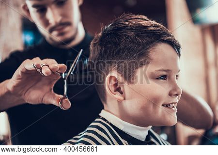 Little Boy Smile While Hairdresser Cuts His Hair.
