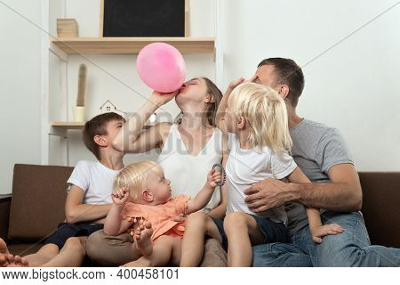 Large Family At Home Preparing For The Holiday And Inflating Balloon