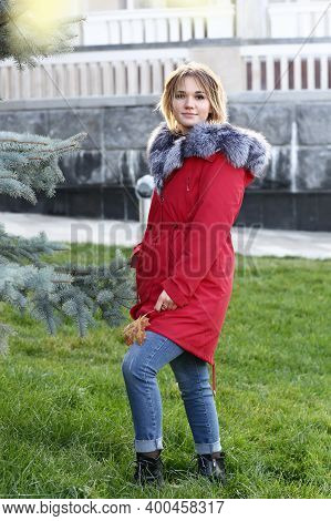 Blond Business Woman In Red Fox Fir Dawn Jacket With Hood Closeup Photo On City Park Background