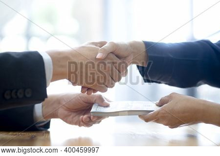 Businessman Shake Hand With Officer And Hold The Cash In His Hand Sign To Give Bribe Concept Corrupt
