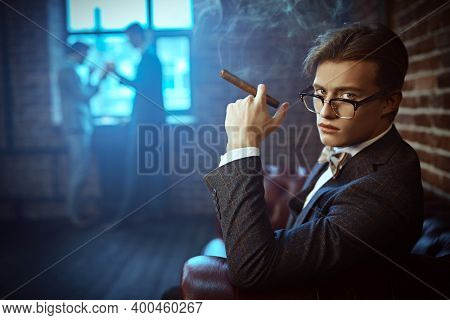 Men's beauty, fashion. Elegant handsome man in an expensive suit and glasses smokes a cigar and spends time in the men's club. Luxury lifestyle.