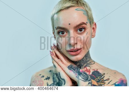 Tattoo And Piercing. Close Up Of A Tattooed And Pierced White Girl Wearing Denim Overall Standing An