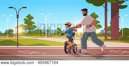 Young Father Teaching Little Son To Ride Bike In Urban Park Parenting Fatherhood Concept Dad Spendin