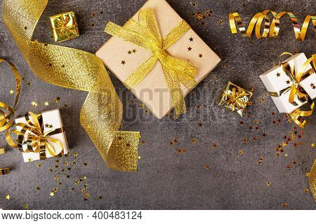 Top View. Bright New Year Card With Golden Christmas Gifts, Serpentine And Ribbon On Dark Background