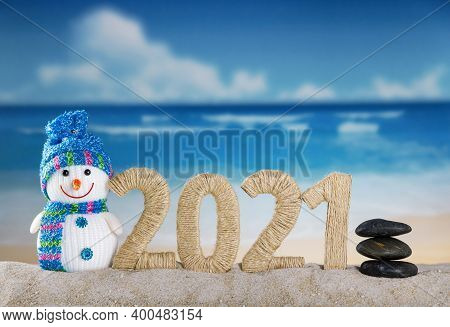 Merry Christmas. Happy Snowman And Lettering 2021 In The Sand On The Beach