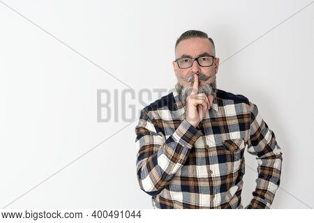 Retro-looking Hipster With Plaid Shirt, Beard, Mustache And Glasses. Sending Silence With The Typica
