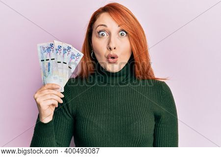 Beautiful redhead woman holding 50 colombian pesos banknotes scared and amazed with open mouth for surprise, disbelief face