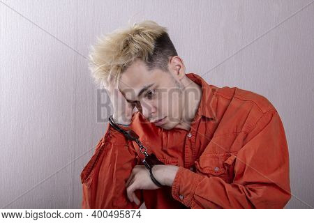 A Teenager In Handcuffs Holds His Head With His Hands On A Gray Background. Headache For Juvenile De
