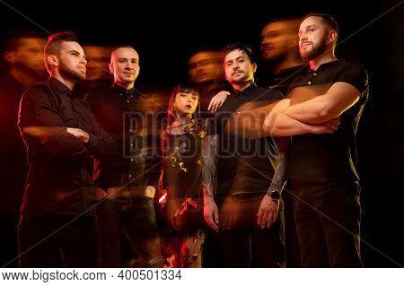 Shadows. Musicians Band Portrait Isolated On Dark Studio Background In Neon Light. Beautiful Caucasi
