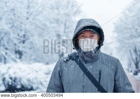 Portrait Of A Man Wearing A Medical Protective Mask On His Face In Winter, Covid-19 Coronavirus Pand