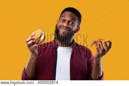 Junk Food Eater. Happy Black Guy Holding Burger And Slice Of Pizza Standing On Yellow Studio Backgro