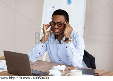 Exhausted Black Manager With Glasses Having Headache While Working In Office In Front Of Laptop, Hav