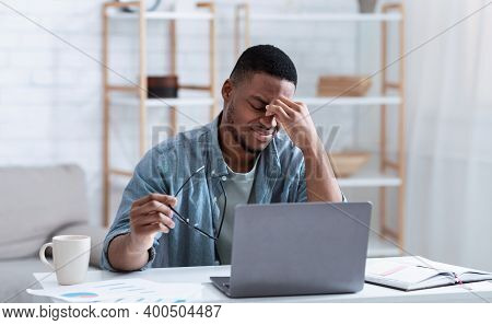 Black Man Suffering From Eyestrain And Eyes Fatigue Massaging Nosebridge Tired After Work On Compute