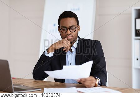 Pensive Black Manager, Businessman Sitting In His Office In Front Of Laptop, Reading Papers Marketin