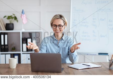 Learning English Online. Happy Female Teacher Giving Foreign Language Lesson On Internet Using Lapto